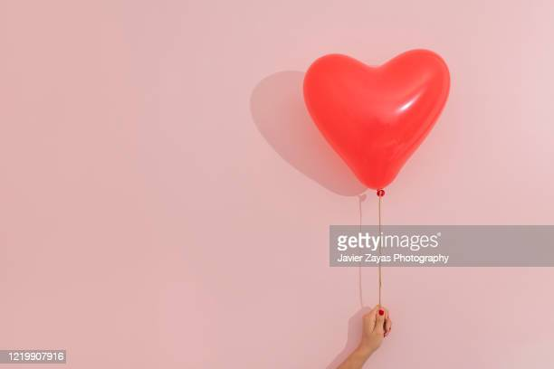 heart shaped red balloon - gesturing stock pictures, royalty-free photos & images