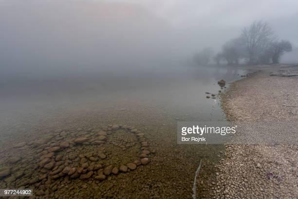 Heart shaped rock arrangement in Bohinj lake in fog, Municipality of Bohinj, Slovenia