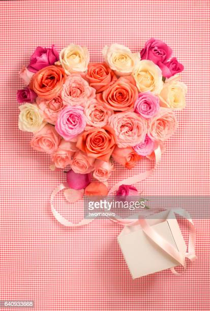 Heart shaped rose bouquet and gift box on pink background.