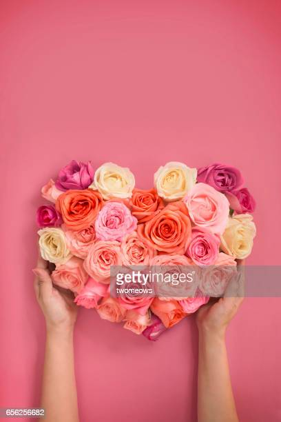 Heart shaped rose bouquet presented by female hands.