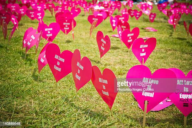 Heart shaped signs printed with the message 'all love is equal'