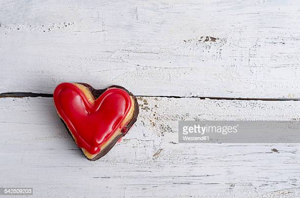 Heart shaped sponge cake on white wood