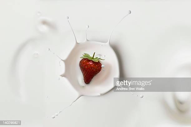 Heart shaped strawberry falling into single cream