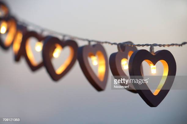 Heart shaped string lights hanging in a row