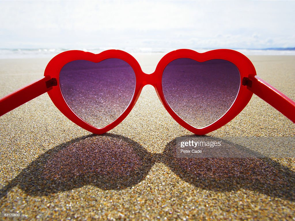 heart shaped sunglasses on beach