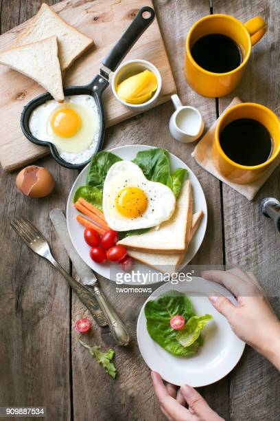 Heart shaped sunny side up breakfast with coffee.