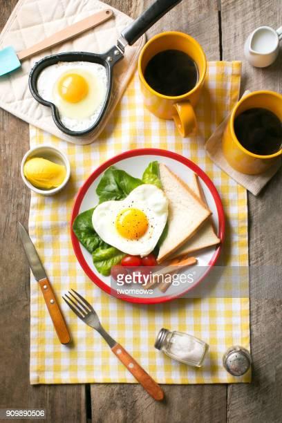heart shaped sunny side up breakfast with coffee. - muttertag herz stock-fotos und bilder
