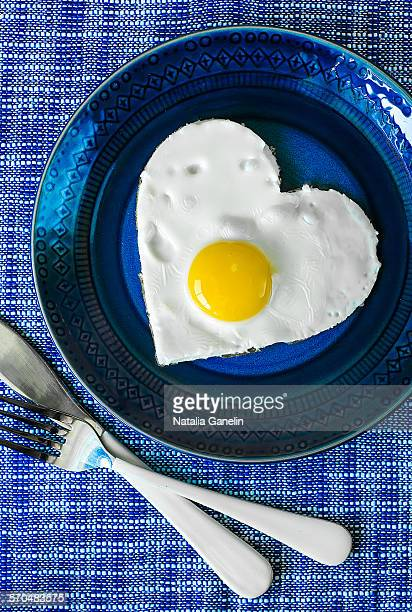 Heart shaped sunny-side up egg on blue plate
