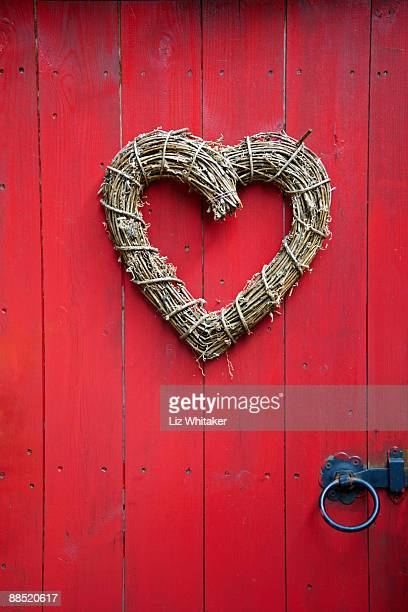Heart shaped wreath on red door, close-up