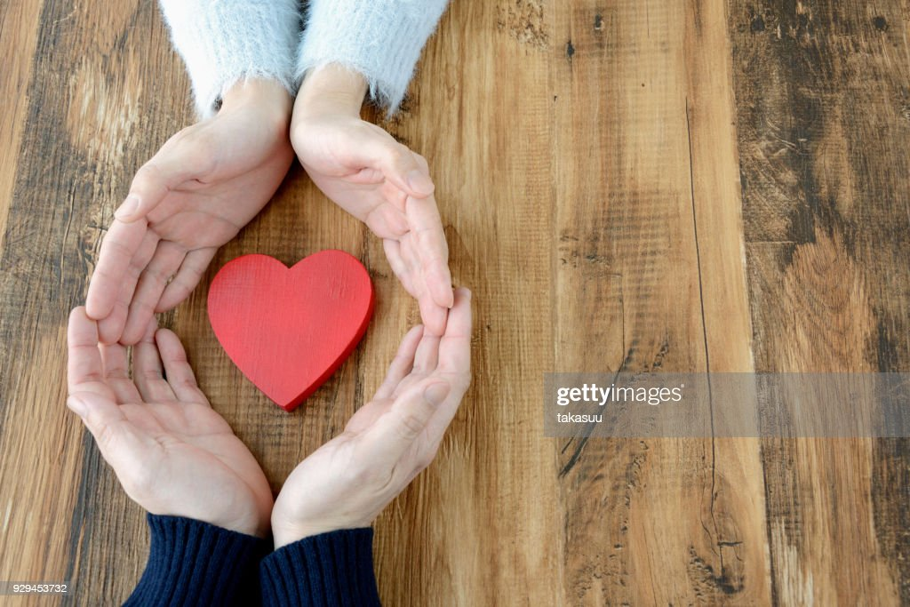 Heart surrounded by man and woman's hand : Stock Photo