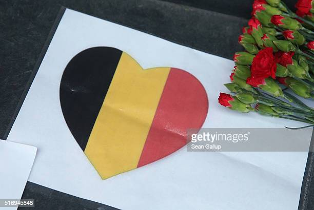 A heart with the colors of the Belgian flag lies among flowers at the steps of the Belgian Embassy following today's terrorist attacks in Brussels on...