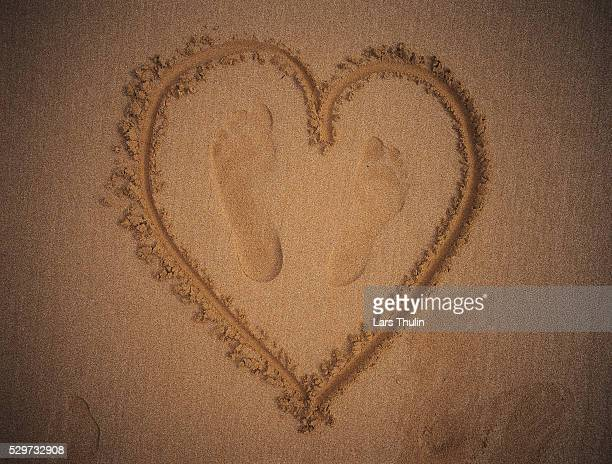 A heart with two footprints carved in the sand on a beach in Morocco