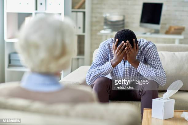 heartbroken patient at psychiatrist - psychiatrist's couch stock pictures, royalty-free photos & images