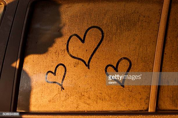 Hearts draw on water of window of a car with shadow of woman