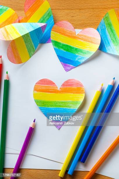 hearts in the colors of the lgbt flag, on a background of white sheets of paper, on a wooden table. bright colored pencils lie nearby. valentines in the color of the rainbow. the concept of lgbt and human rights, valentine's day. - valentine' day stock pictures, royalty-free photos & images