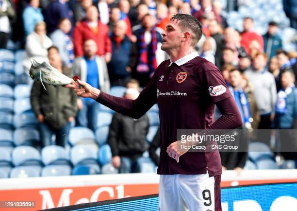 Hearts' Kyle Lafferty throws his boot to a young fan in the away section at full time
