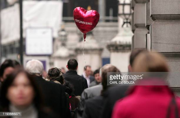 A heartshaped balloon is carried through the crowds on Valentines Day in central London on February 14 2008 Sending Valentine's Day ecards to work...