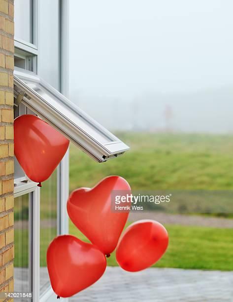 Heart-shaped balloons outside window