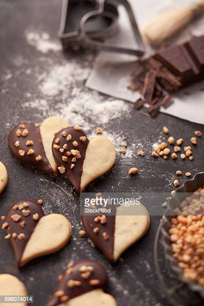 Heart-shaped biscuits with chocolate glaze and chopped nuts