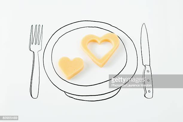 Heart-shaped cheese on drawing of plate