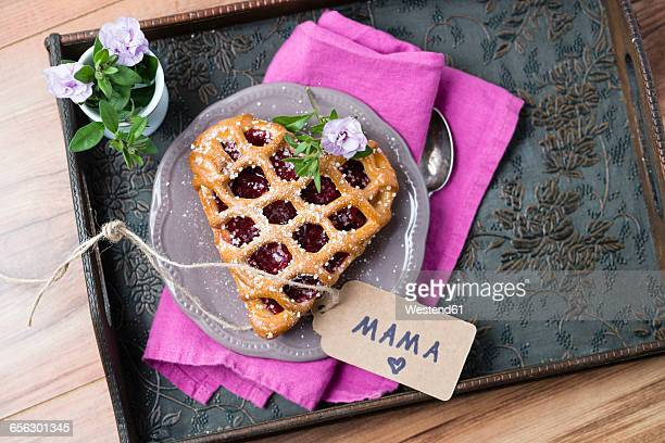 Heart-shaped cherry cake with name tag and flowers on tray