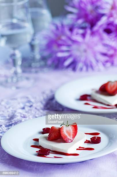 Heart-shaped coconut jelly with fresh strawberries and strawberry and cranberry coulis