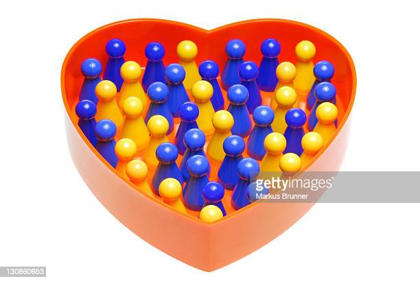 Heart-shaped container with meeples in two colours, symbolic image of partner search