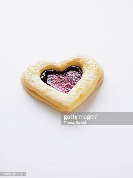 Heart-shaped cookie with raspberry filling, elevated view