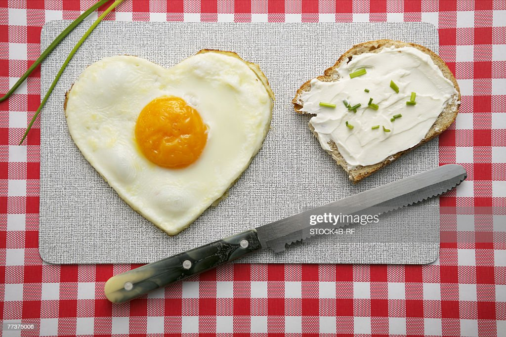 Heart-shaped fried egg and a bread with cream cheese : Photo