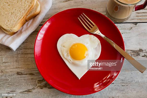 Heart-shaped fried egg on red plate