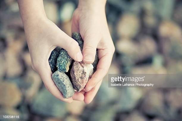 Heart-shaped hands holding rocks