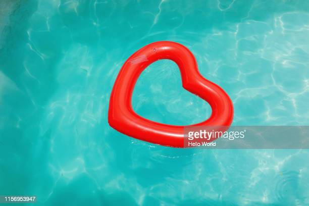heart-shaped inflatable in crystal clear water - red tube stock pictures, royalty-free photos & images
