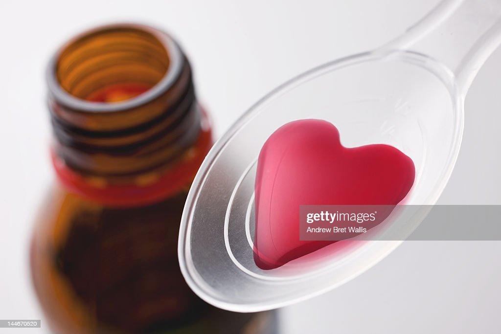 Heart-shaped liquid medicine on a spoon : Stock Photo