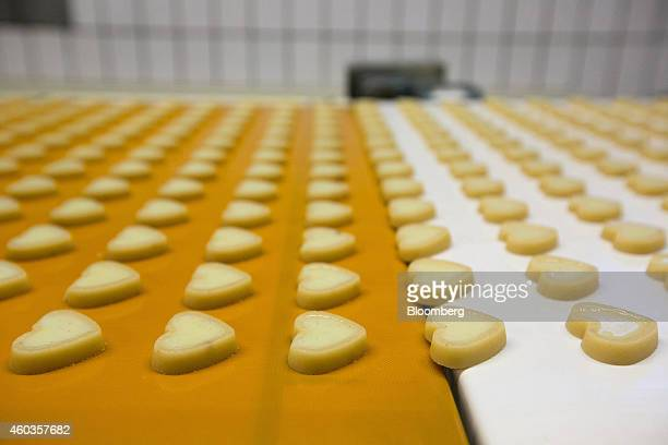 Heartshaped marzipan filled with champagne truffle pass along a conveyor belt inside the factory of traditional confectionary maker JG Niederegger...