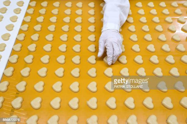 Heartshaped marzipan pass along a conveyor belt at the headquarters of the traditional confectionary maker JG Niederegger GmbH in Luebeck Germany on...
