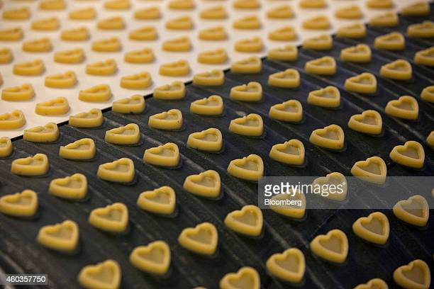 Heartshaped marzipan sweets pass along a conveyor belt before being filled with chocolate inside the factory of traditional confectionary maker JG...