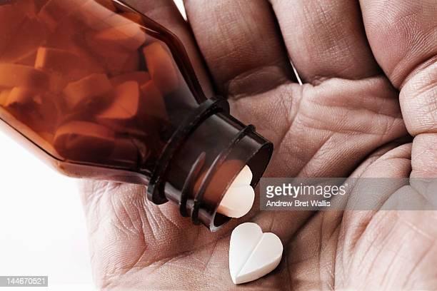 Heart-shaped pills shaken onto a man's palm