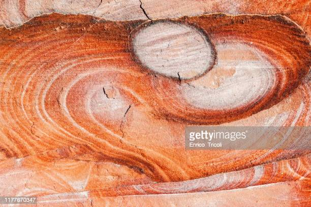 heart-shaped rock face, colored red yellow and orange, photographed in the caves of petra in jordania. - fossil stock pictures, royalty-free photos & images