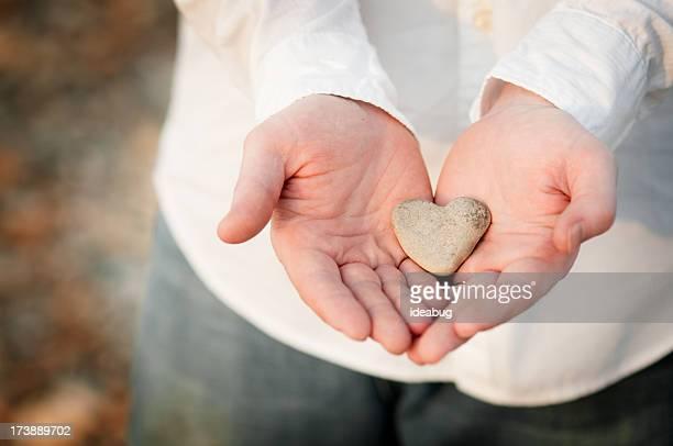 En forme de cœur dans une roche homme mains