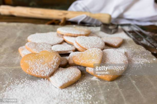 Heart-shaped shortbreads sprinkled with icing sugar on parchment paper