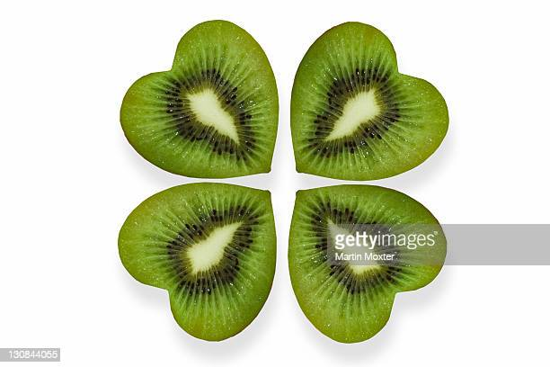 heart-shaped slices of kiwi fruit arranged like a cloverleaf - 4 leaf clover stock-fotos und bilder