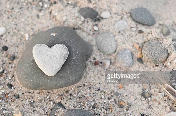 Herzförmigen Stein mit anderen Felsen am Strand Sand
