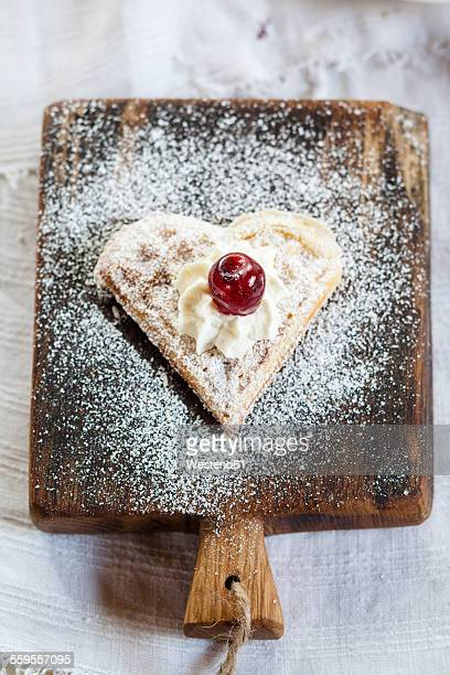 Heart-shaped waffle with whipped cream and cherry on cutting board
