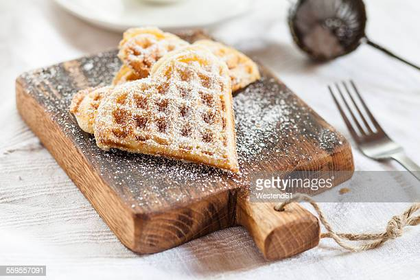 Heart-shaped waffles on cutting board