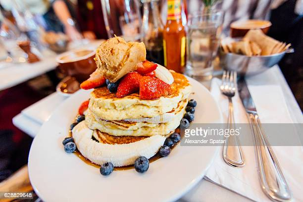 Hearty stack of pancakes with maple syrup, banana, strawberry and blueberry on the plate, served in a diner