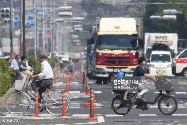 Heat haze distorts the background as bicyclists ride past during a heatwave in Tokyo on August 9 2017 / AFP PHOTO / Kazuhiro NOGI