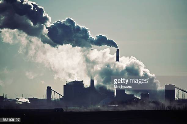 Heat, steam and smoke rising from the chimneys of a power plant against the sky.