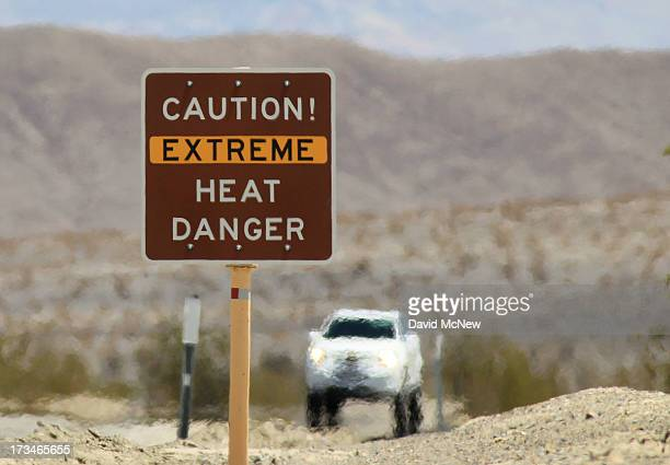 Heat waves rise near a heat danger warning sign on the eve of the AdventurCORPS Badwater 135 ultramarathon race on July 14 2013 in Death Valley...