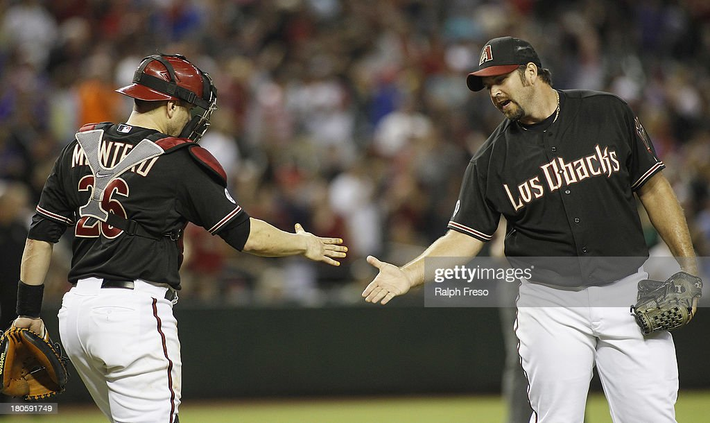 Heath Bell #21 of the Arizona Diamondbacks is congratulated by catcher Miguel Montero #26 after pitching the ninth inning against the Colorado Rockies during a MLB game at Chase Field on September 14, 2013 in Phoenix, Arizona. The Diamondbacks defeated the Rockies 9-2.