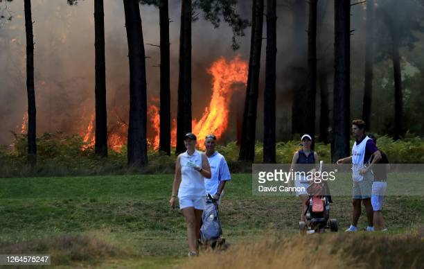 Heath fire behind the tenth tee stops play as the group of Cara Gainer, Sophie Powell and Gabriella Cowley wait to play off during day three of The...